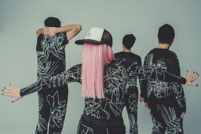 Na pierwszym planie kobiet w różowych włosach, czapce z czarnymi paznokciami rozpościera ręce. Na drugim planie trzy osoby w czapkach odwrócone tyłem. Wszyscy ubrani w czarne stroje w białe bohomazy.