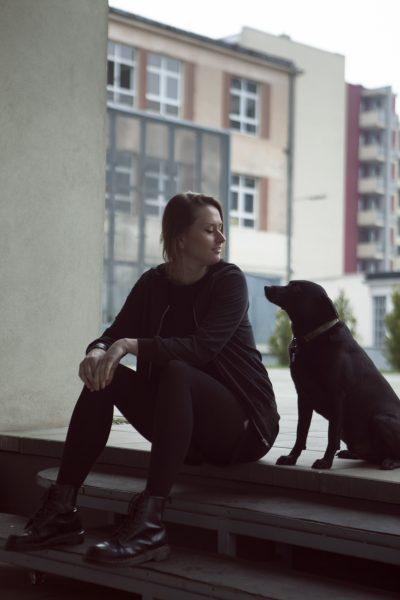 Kobieta i pies siedzą na schodach, są zwróceni ku sobie. W tle niski budynek.